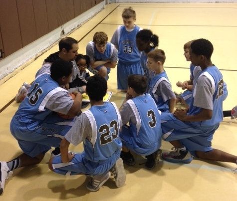 A coach talks to his team during a CAAEL basketball game