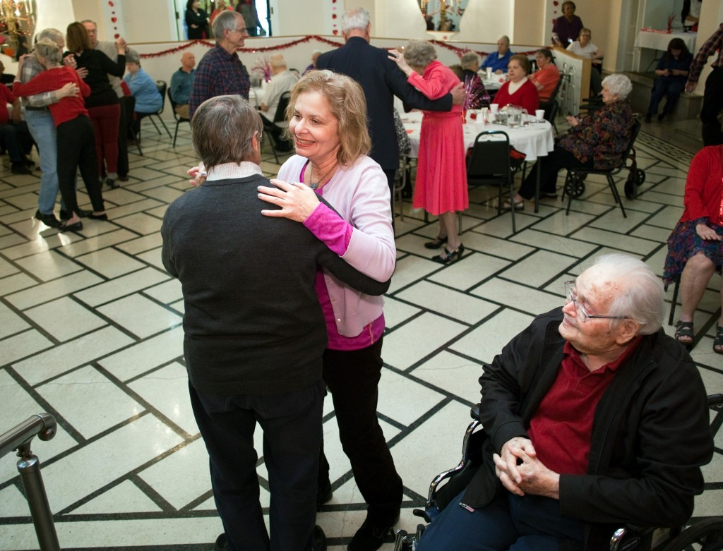 Oak Park Arms resident Leo Rich, right, watches his daughter Arlene Stuckenbrock dance with Dr. Reid Owen during Oak Park Arms Valentine's Day Ballroom Dance.